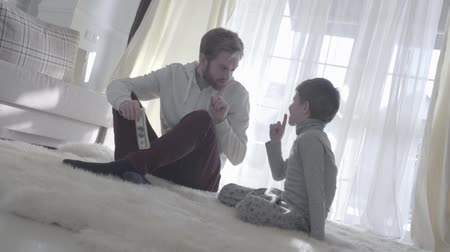 камин : Playful dad sitting with his son at the carpet and holding money. Man and boy put a finger to the nose. Father agrees with the child. Father-son relationship.