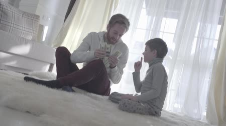 silenzio : Playful beard father sitting with his son at the carpet and holding money. Dad and kid put a finger to the nose. Joyful daddy counts money. Father-son relationship.