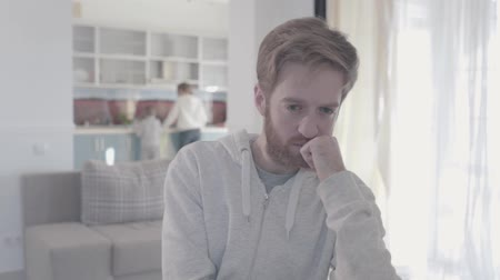 quarreling : Portrait of sad bearded man standing in living room close up. Woman and boy are in the background. Family relationships. Family problems. Slow motion. Stock Footage