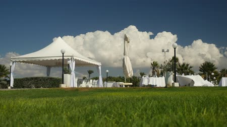 tentáculo : Empty buffet in nature made in white colours. Landscape is picturesque. Green grass, blue sky, empty place Stock Footage