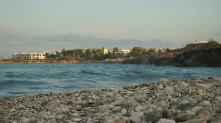 subtropical : Small waves crashing an empty beach creating sea foam on the background of the cityscape. Cyprus coast summer day.