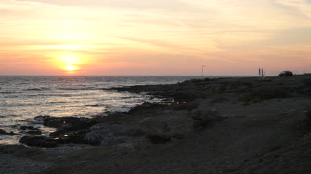 água do mar : Beautiful colorful sunset on the Mediterranean sea beach. Alone car parked in beautiful picturesque place to contemplate the landscape.