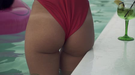 feliz : View of pretty girl with beautiful wet ass in bikini standing in swimming pool and preparing for swimming. Leisure and fun of girl.