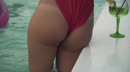 bum : Closeup view of pretty girl with beautiful wet ass in bikini standing in swimming pool and preparing for swimming