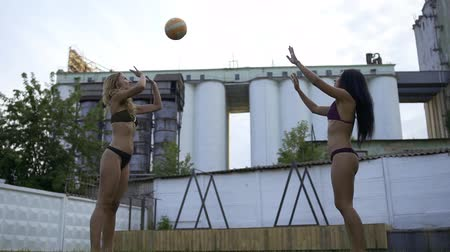 feliz : Two beautiful girls playing volleyball in sexy bikini outdoor. Rest of two sexy girlfriends in swimsuits. Slow motion.