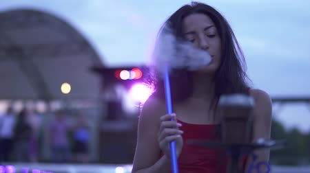 дубленый : Beautiful brunette smokes a hookah, dances and enjoys the evening on the outdoor lounge.