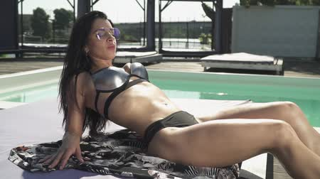 кавказский : Pretty woman in swimmimg suit is sunbathes laying near swimming pool. Leisure of beautiful lady in a bikini and sunglasses relaxing on a lounger.