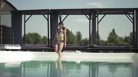 nudité : Brunette woman in shiny silver swimming suit on athletic body goes into the water in the swimming pool. Leisure of lonely lady in a bikini. Vidéos Libres De Droits