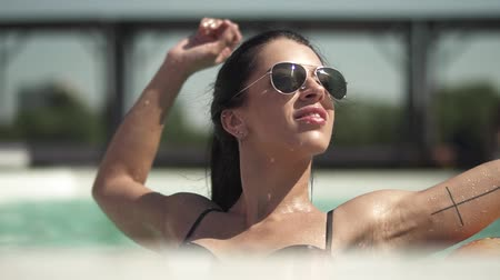 nudité : Portrait of beautiful woman in sunglasses swimming in the pool. Leisure of lonely lady in a bikini. Vidéos Libres De Droits