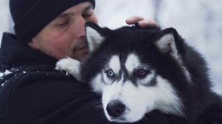 tur : Portrait of a man in winter outerwear hugging and stroking a husky outdoors. Guy with his pet.