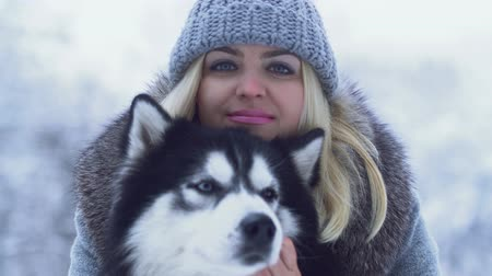 loajální : Portrait of beautiful young woman holding and hugging fluffy siberian husky in the winter snow background. Dog on a winter walk in the forest.