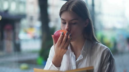 biblioteca : Portrait of beautiful healthy girl biting an apple and attentively reading a book in a cafe on the urban background