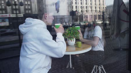drinking coffee : Couple on a date sit in a cozy cafe and drink coffee, and on their round table lies green apple and stands a flower Stock Footage