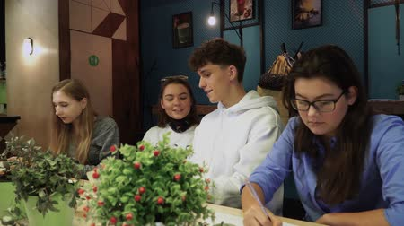 toilet paper : Four classmates sat at the tables and worked on something, and then they noticed that they are photographed, they began to smile and raise their big fingers up Stock Footage