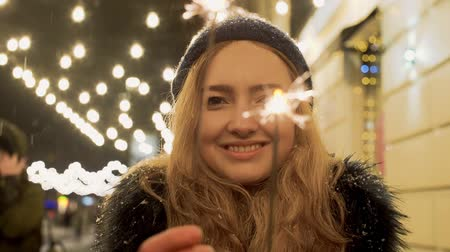 giymek : Portrait of retty young woman with sparklers in hands close up. Sparks scatters in different directions