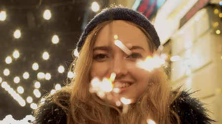 рассеянный : Portrait of cheerful young woman with sparklers in hands close up. Sparks scatters in different directions