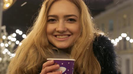 латте : Portrait of a beautiful smilling young girl with long blond hair standing in a winter jacket on a winter street and holding a cardboard cup of hot tea in her hands.