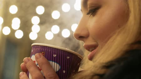 латте : Woman lips blowing on steam from paper coffee cup outdoors. Lady is smiling close up