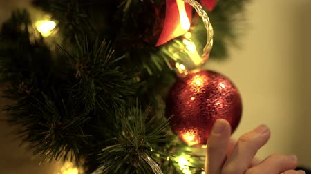 ornamentação : Female hand touches red christmas toy hanging on the tree close up