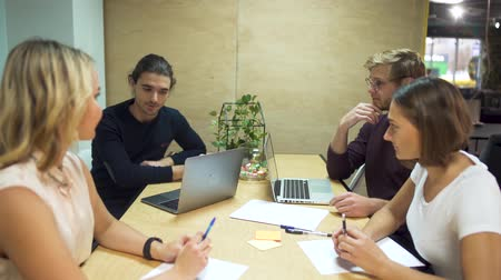 proposta : Four young entrepreneurs discuss new strategies in start-up using laptops in office meeting room