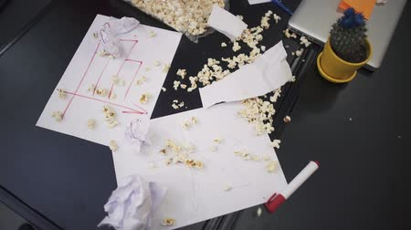 crumpled flower : Popcorn and crumpled sheets of paper falling down in slow motion on the charts with financial indicators lying on the table. Stock Footage