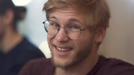 připomínka : Bearded guy with glasses shares his impressions conveying his emotions from the meeting at the discussion table with his partners.