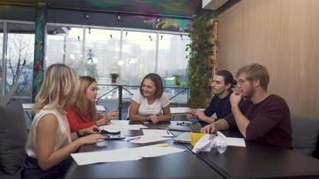 çözme : Team of young successful entrepreneurs meeting at boardroom table discussing financial report. Table for discussions standing on the background of a large window through which city traffic is visible. Stok Video
