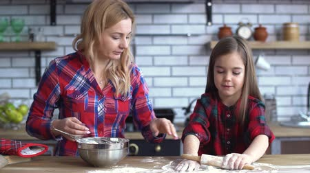 кнут : Beautiful young mother with blond long hair mixing in plate and small cute naughty girl play with flour on the kitchen table