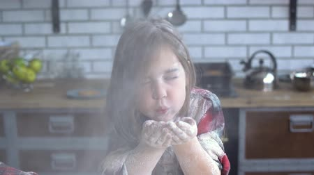 nepořádek : Portrait of a little girl heavily soiled in flour blowing flour from her palm. Cute girl having fun in the kitchen. Dostupné videozáznamy
