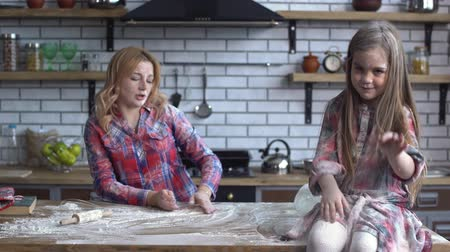 fool : Young blond mother with dirty messy all in flour daughter play with flour in the kithen table Stock Footage