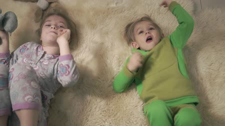 fofinho : Cute small kids in pajamas rolling on the floor with fluffy carpet. Brother and sister have a fun. Happy kids weekend. Stock Footage
