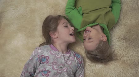пижама : Cute little kids in pajamas lying on the floor with fluffy carpet. Brother and sister have a fun together. Happy siblings weekend. Стоковые видеозаписи