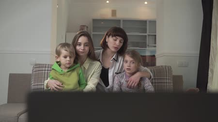 displeasure : Two older sisters with sad faces and a younger sister and brother sitting on the couch in the guest room and watch TV. Family holiday. Stock Footage