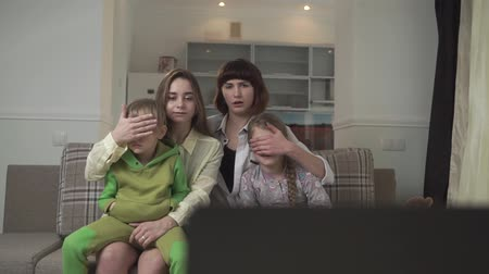 displeasure : Family watch TV. Older sisters close their eyes to children because of bad inappropriate content on the screen. Native people spend time together. Family holiday. Stock Footage