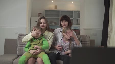 watch tv : Family watching TV sitting on the couch in the guest room. Older sisters close their eyes to children because of bad inappropriate content on the screen. Native people spend time together. Family holiday. Stock Footage