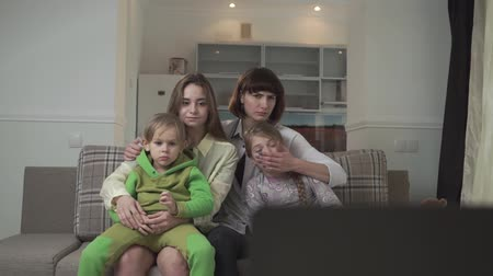 displeasure : Family watching TV sitting on the couch in the guest room. Older sisters close their eyes to children because of bad inappropriate content on the screen. Native people spend time together. Family holiday. Stock Footage