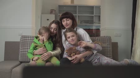 okşamak : Happy family of four members watch TV. Small boy is tired and rubs his eyes Stok Video