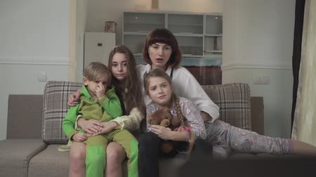привет : Family sitting on the couch in the guest room and watching TV expressive and emotionally. Older sisters and younger siblings spend time together. Family holiday. Стоковые видеозаписи