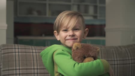 fofinho : Portrait of a little cute cheerful boy in pajamas hugging a teddy bear standing in the living room. Happy joyful child. Slow motion.