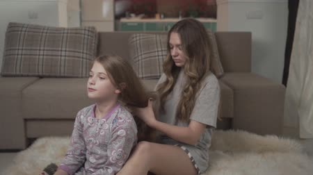 sitting floor : Older sister combing hair of younger girl sitting on the floor on fluffy carpet near couch. Sisters relationship. Stock Footage