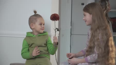 давать : Little boy in green pajamas gives flower to his sister. Family relationship