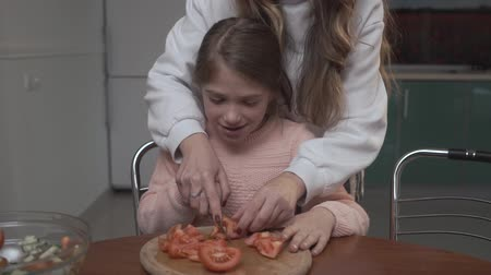 kin : Older girl teaches younger girl to cut tomatoes for salad. Two sisters cocking vegetable salad while sitting at the table in the kitchen. Sisters relationship. Stock Footage