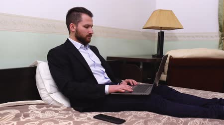 beardie : Handsome businessman in suit sitting in bed with laptop. Handsome bearded man working in bedroom.
