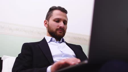 beardie : Handsome man texting on laptop. Bearded businessman working at home.