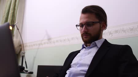 beardie : Handsome man with glasses works at laptop at home Stock Footage