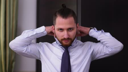 iyi giyimli : Portrait of bearded man with modern haircut tying a tie looking in camera. Stok Video