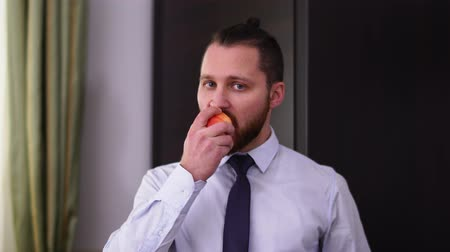beardie : Portrait of bearded man with modern haircut biting and chewing an apple looking in camera