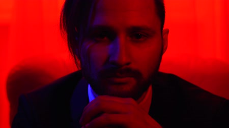 beardie : Portrait of a successful bearded businessman dressed in a business suit in bright red light. Stock Footage