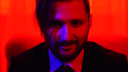 beardie : Portrait of a business bearded smiling man dressed in a business suit sitting in bright red light. Stock Footage