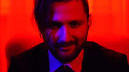 para a frente : Portrait of bearded smiling man looking in camera. Shooting in red light